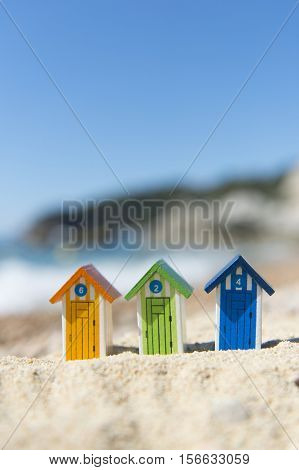 Colorful striped wooden beach cabins at the coast