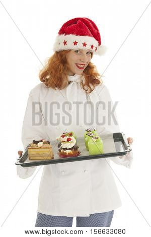 Female baker chef with red hat of Santa Claus baked Christmas pastries isolated over white background