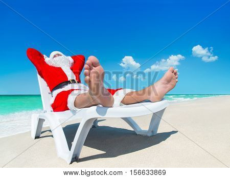 Christmas Santa Claus sunbathe on sunlounger at tropical ocean beach heels at foreground - New Year travel vacation in hot countries concept