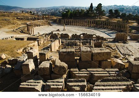 Photo of the Ruins with building blocks sanctuary of Zeus Olympios and Oval Forum antique town Gerasa. Modern Jerash on background.Tourist attraction, vacation and sightseeing concept.