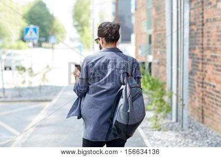 people, technology, travel and tourism - man with backpack, smartphone and earphones walking along city street and listening to music