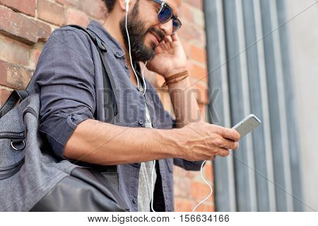 people, technology, travel and tourism concept - close up of man with earphones, smartphone and bag listening to music on street