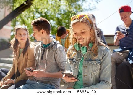technology, internet and people concept - group of happy teenage friends with smartphone and headphones outdoors