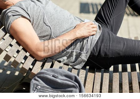 people, technology, leisure and lifestyle - close up of man with smartphone, earphones and backpack listening to music lying on city street bench