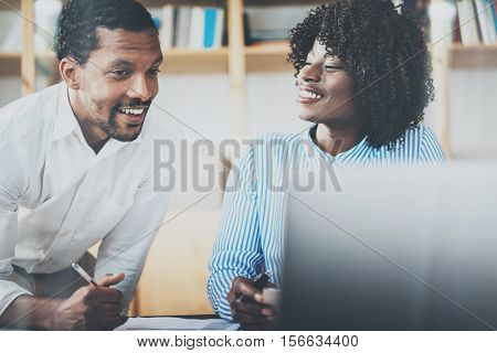 Group of two young coworkers working together in a modern coworking studio.African black business partners using laptop and discussing new startup project.Horizontal, blurred