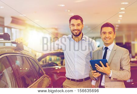 auto business, car sale, techology and people concept - happy man and car dealer with tablet pc computer in auto show or salon