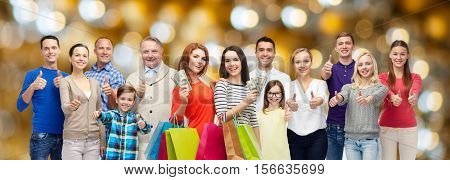 sale, family, generation and people concept - group of happy men and women with shopping bags and money showing thumbs up over holidays lights background