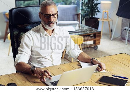 Adult successful businessman wearing a classic glasses and working at the wood table in modern coworking studio.Stylish bearded middle age man using laptop on workplace. Horizontal, blurred background