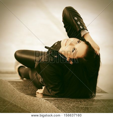 Young woman in leather jacket lying on city street. Stylish fashion model outdoor