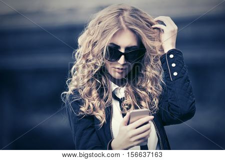 Business woman in sunglasses calling on mobile phone. Fashion stylish model outdoor