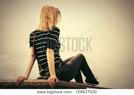 Young woman sitting against a cloudy sky. Stylish fashion model outdoor