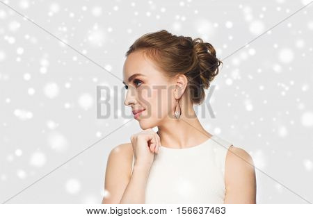 jewelry, luxury, christmas, holidays and people concept - smiling woman in white dress wearing pearl earrings over gray background and snow