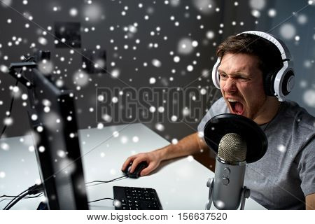 technology, gaming, entertainment, let's play and people concept - angry screaming young man in headset with pc computer playing game at home and streaming playthrough or walkthrough video over snow