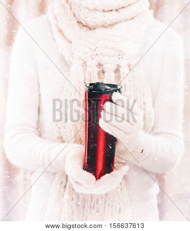 Woman holds a winter cup close up. Woman hands in woolen red gloves holding a thermo mug with hot cocoa, tea or coffee and a candy cane. Winter and Christmas time concept.