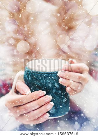 Woman holds a winter cup close up. Woman hands with elegant french manicure nails design holding a cozy knitted mug. Winter and Christmas time concept.