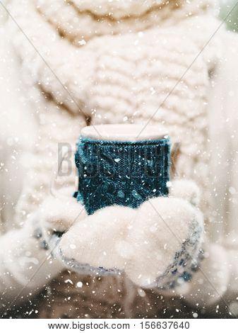 Female hands holding knitted winter mug close up. Woman hands in white and blue mittens holding a cozy knitted cup with hot cocoa, tea or coffee. Winter and Christmas time concept.