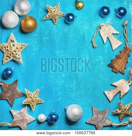Christmas or New Year holiday background. Decoration wooden and glittering Christmas tree toys and balls over bright blue wooden background, top view, copy space in center