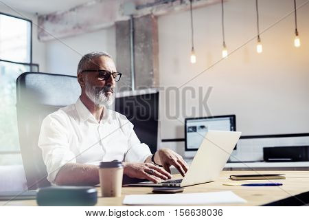 Middle age financial analyst wearing a classic glasses and working at the wood table in modern interior design office.Stylish bearded businessman using laptop on workplace. Horizontal, blurred