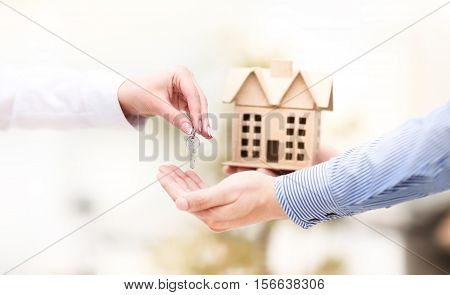 Woman is handing a house key to a man.