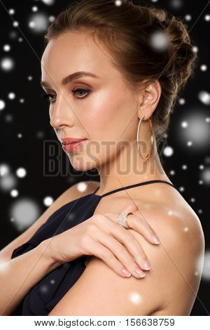 people, luxury, christmas, holidays and jewelry concept - beautiful woman wearing diamond earring and ring over black background and snow