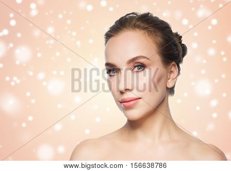 beauty, people, winter and health concept - beautiful young woman face over beige background and snow