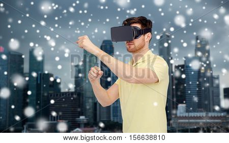 technology, augmented reality, winter, christmas and people concept - young man with virtual headset or 3d glasses playing game and fighting over singapore city background