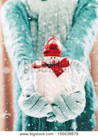 Woman holding winter cup with nice Christmas toy close up on light background with snowfall. Hands in woolen teal gloves holding a cozy mug with happy snowman toy. Winter and Christmas time concept.
