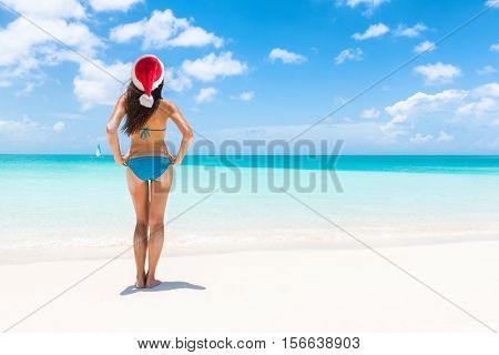Christmas holiday santa hat bikini woman relaxing on paradise beach island getaway.