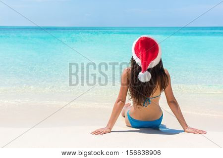 Christmas beach vacation santa claus hat woman. Tropical holiday bikini girl sitting down on white sand at paradise travel destination relaxing on paradise island getaway.