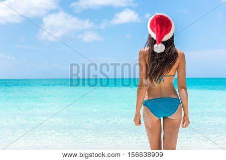 Christmas holiday santa hat bikini woman relaxing on paradise beach island getaway.