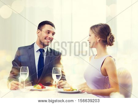 restaurant, couple and holiday concept - smiling couple eating main course at restaurant