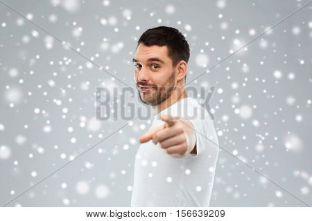 gesture, winter, christmas and people concept - man pointing finger to you over snow on gray background