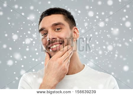 beauty, grooming, winter, christmas and people concept - happy young man touching his face or beard over snow on gray background
