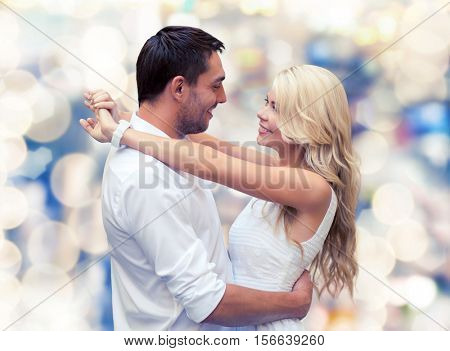 holidays, people, love and dating concept - happy couple hugging over lights background