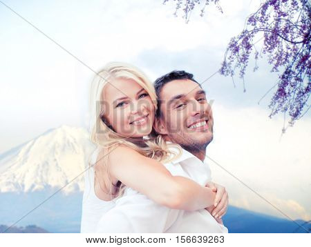 vacation, travel, honeymoon, people and tourism concept - happy couple having fun over fuji mountain background
