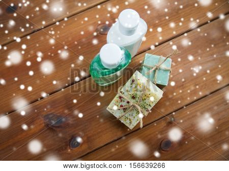 beauty, spa, bodycare, bath and natural cosmetics concept - handmade soap bars and lotion bottles on wood over snow