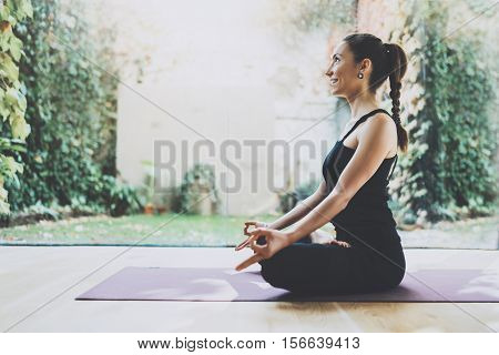 Portrait of gorgeous young woman practicing yoga indoor. Beautiful girl practice lotus position in class.Calmness and relax, female happiness.Horizontal, blurred background
