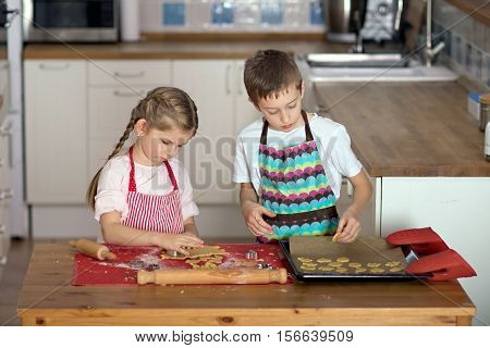 Girl and boy cutting shapes of shortcut pastry making biscuits in the kitchen