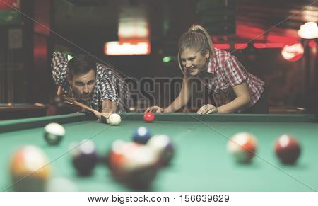 Couple playing snooker and having fun together