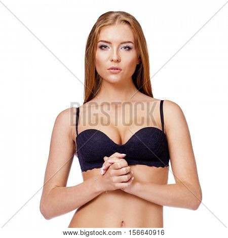 Calm young blonde woman posing in bikini over white background