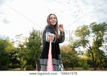 Happy beautiful young woman playing with dog on leash in park