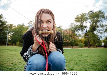 Funny young woman with bone in mouth playing with dog in park