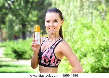 Sporty woman holding sunscreen on blurred nature background