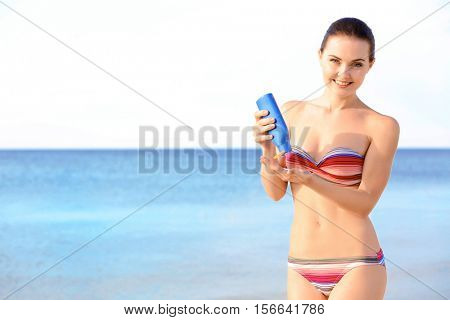 Young beautiful woman holding sun protective lotion on the beach