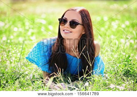 Portrait of young woman lying in green grass