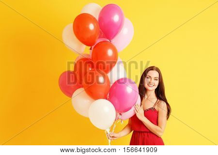 Beautiful young woman with air balloons on yellow background