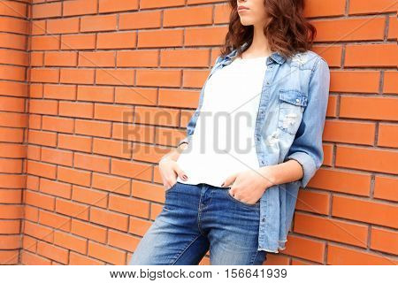 Young woman in blank t-shirt leaning against brick wall, closeup