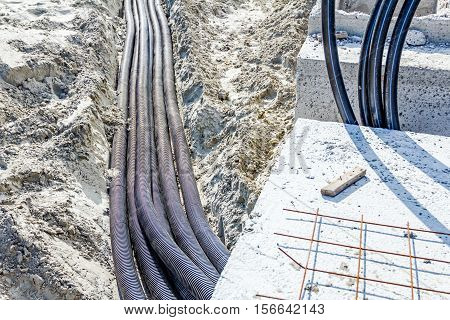 Bundle of corrugated hoses are placed in sandy trench.
