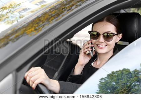 Beautiful woman with cellphone driving a car