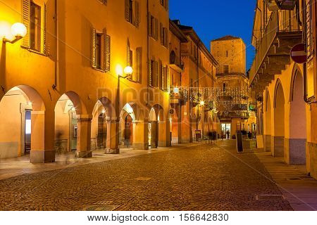 Evening view of narrow cobblestone street in town of Alba in Piedmont, Northern Italy.